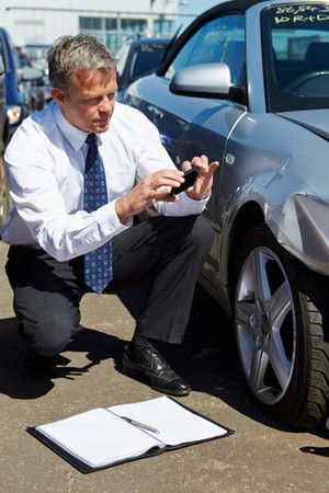post accident rehabilitation course man with camera kneeling by  car to assess collision damage to the front wing